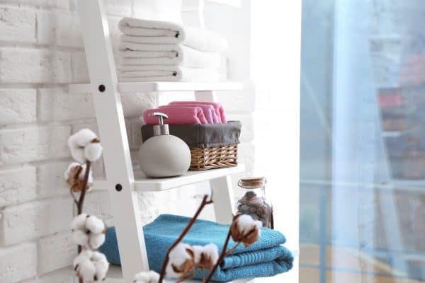 bathroom ladder with towels, soap and a wicker basket