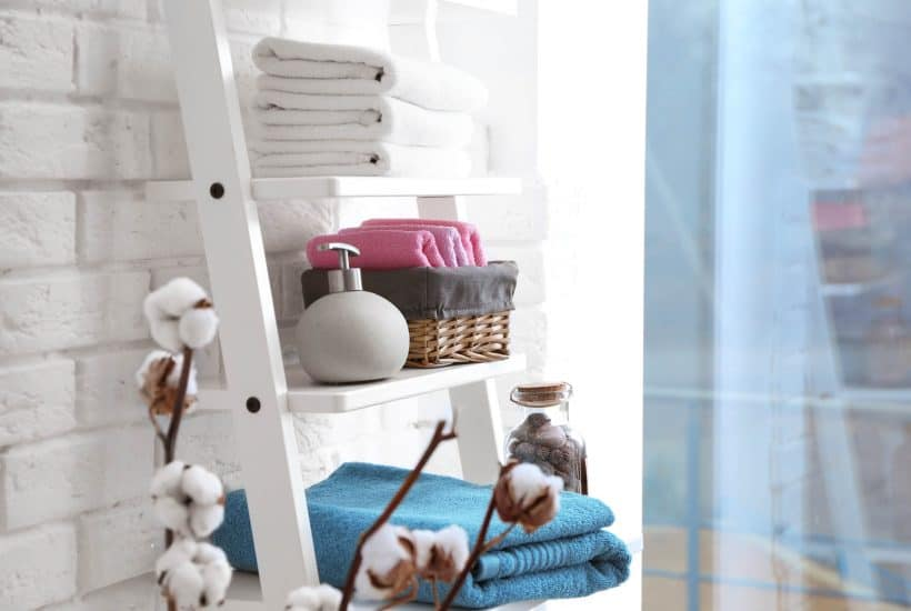 bathroom storage ladder with towels, soap and a storage basket