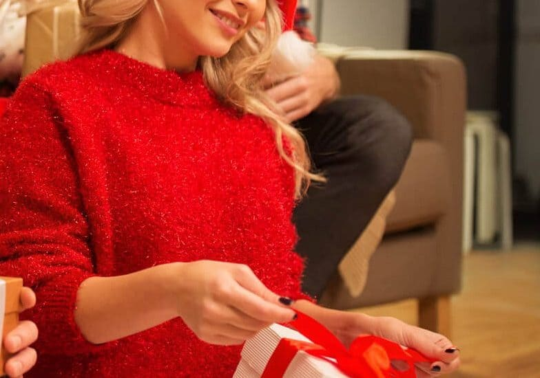 Woman in red sweater and Santa Hat opening a gife