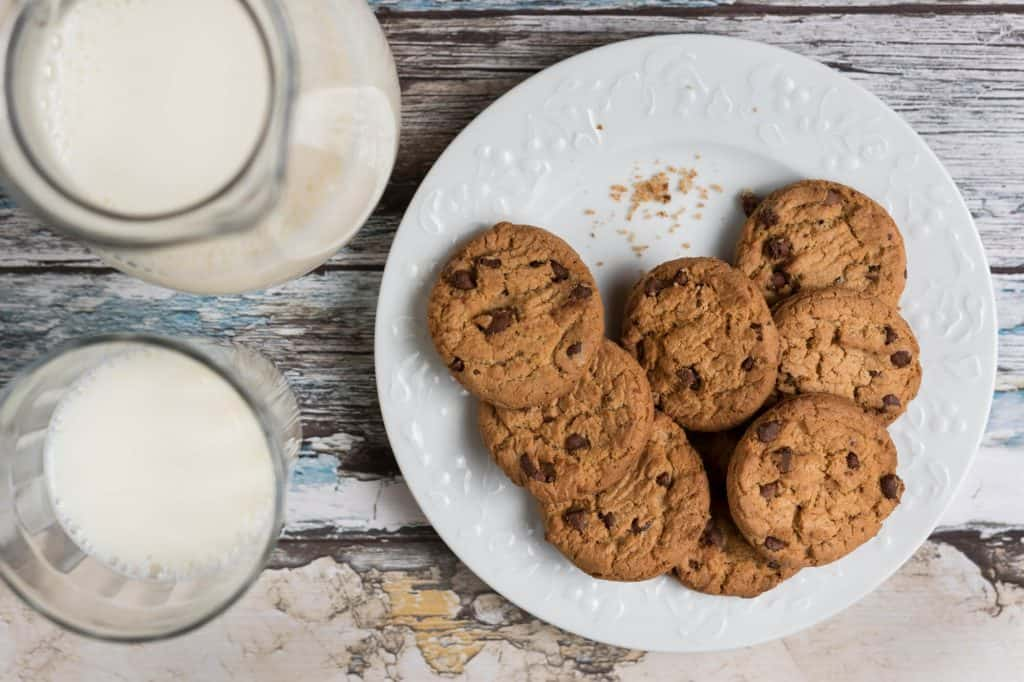 Plate of chocolate chip cookies and two glasses of milk