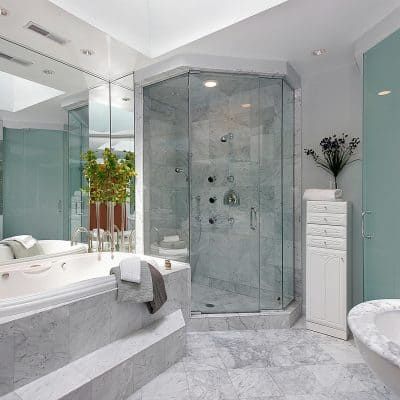 Clean tub, sink and toilet in a marble master bathroom