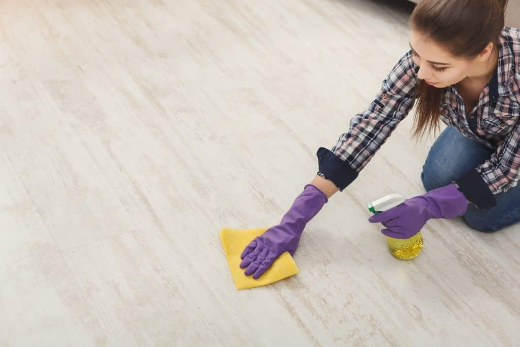 woman cleaning vinyl floor smudges with rubbing alcohol cleaning tip