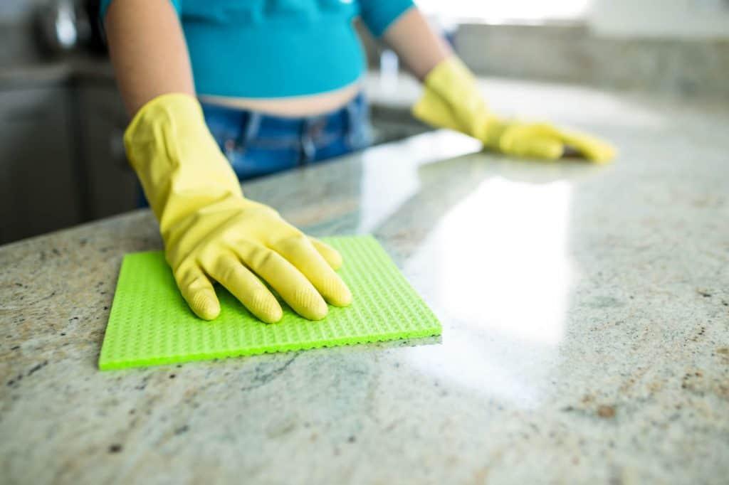 woman cleaning granite countertop