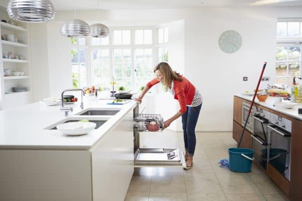 Woman loading dishwasher and following her cleaning schedule checklist