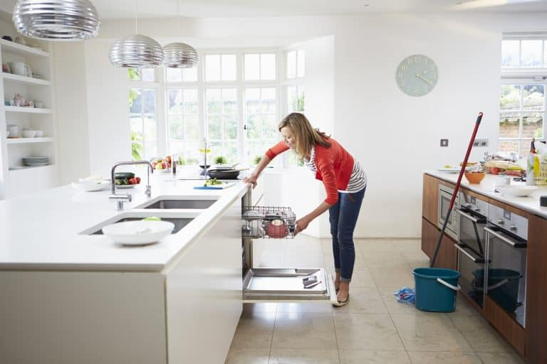 Woman loading dishwasher and cleaning
