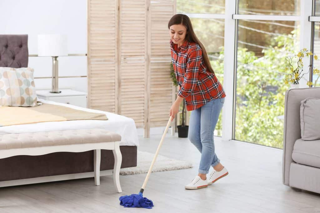 woman mopping bedroom floor while cleaning