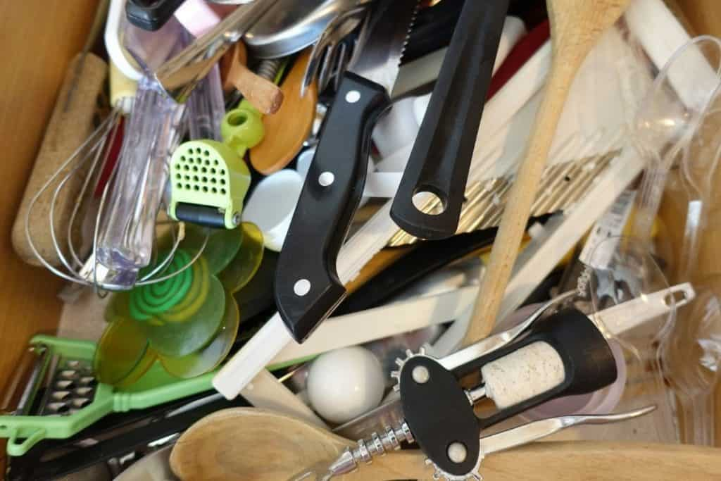 a cluttered kitchen utensil drawer is a decluttering task that could be completed quickly