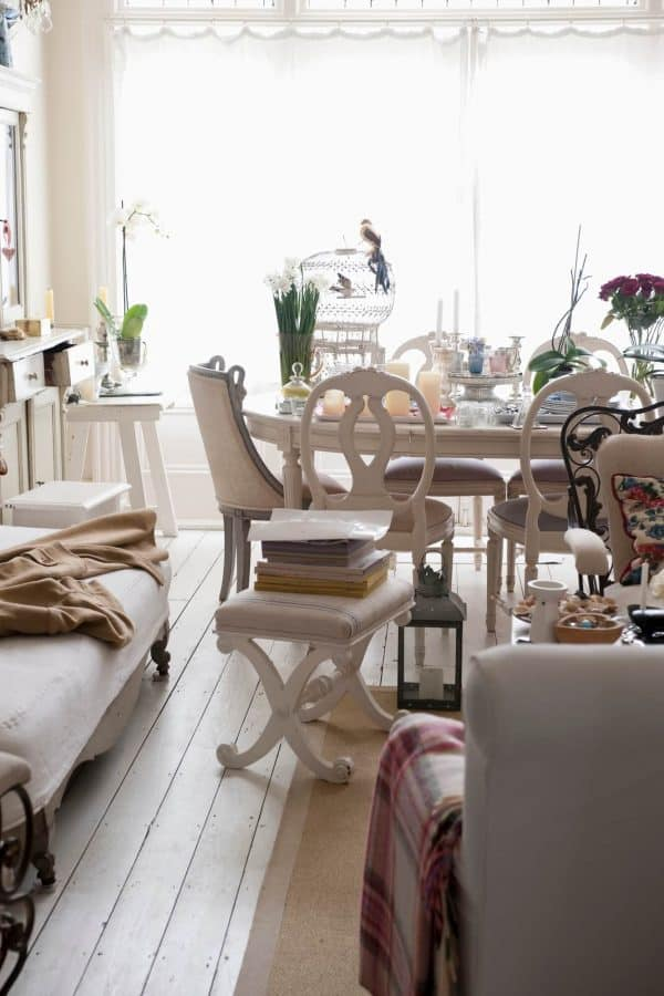 cluttered dining room with lots of books and decor items all over the place that can be dealt with by asking these decluttering questions