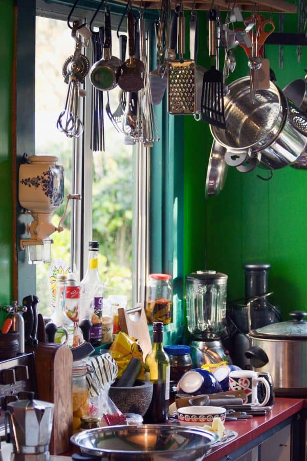 cluttered kitchen with lots of pots, pans, dishes, and small appliances on the counters