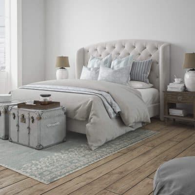 Decluttered bedroom with a neatly made bed, storage trunks and an area rug