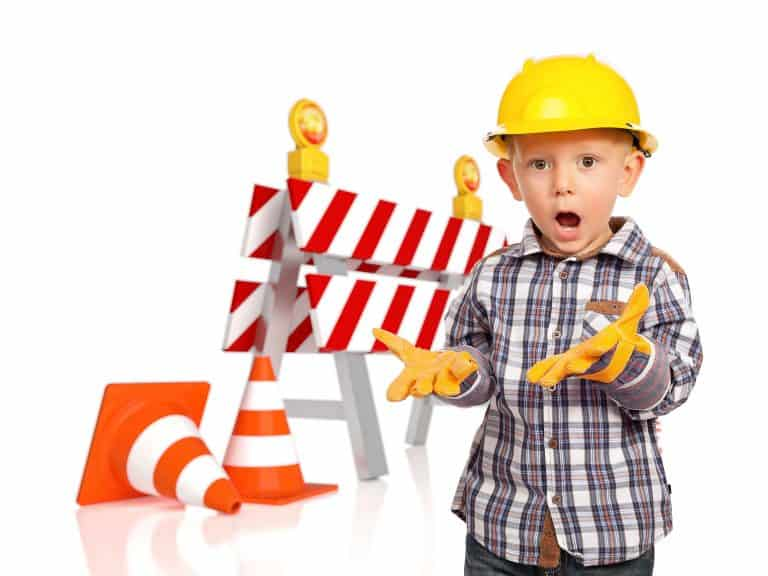 little boy in hard hat, gloves, and shocked expression standing next to a roadblock saw horse and orange construction cones