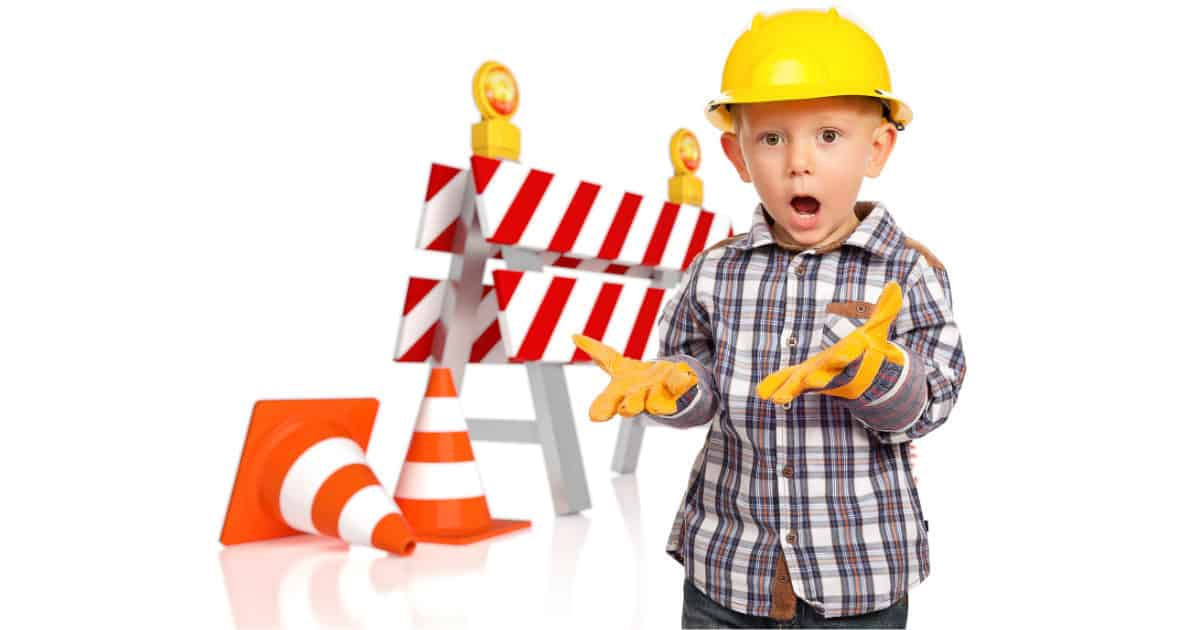 shocked young boy in construction hat standing in front of roadblock