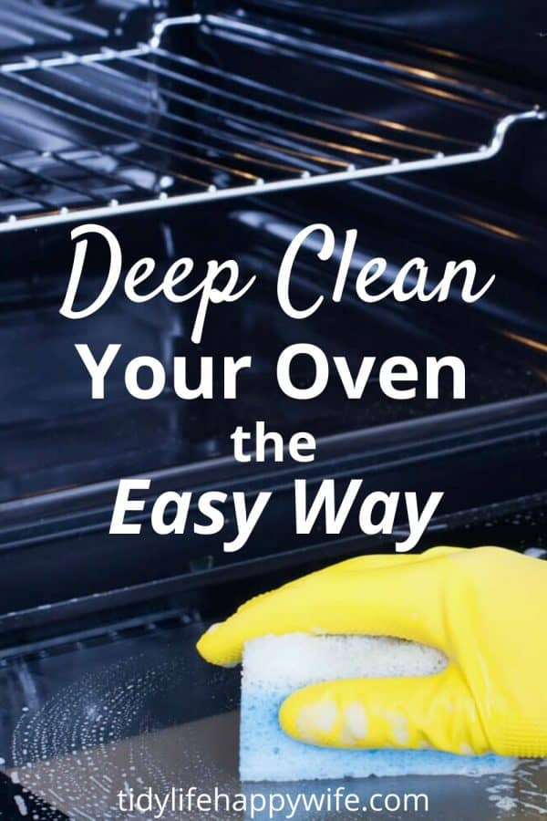 Gloved hand with sponge deep cleaning an oven.