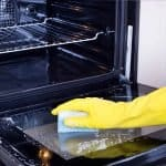 Gloved hand with sponge deep cleaning the oven.