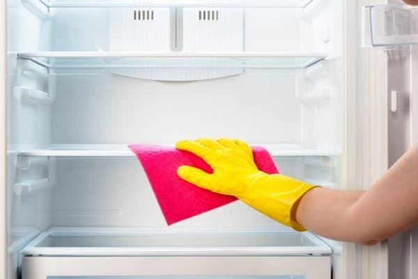 woman cleaning inside the refrigerator with microfiber cloth