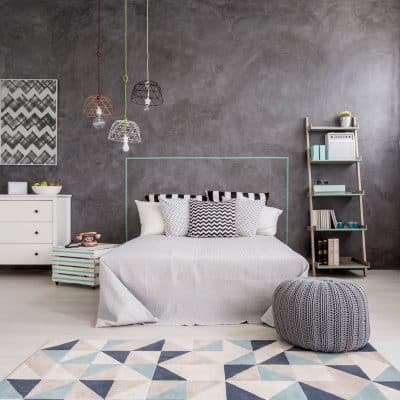 Gray bedroom with dressers and shelving for extra storage