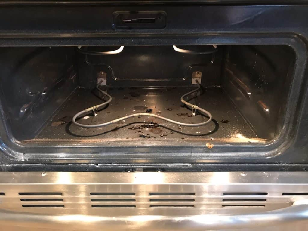 Dirty oven with burnt on food before being cleaned.
