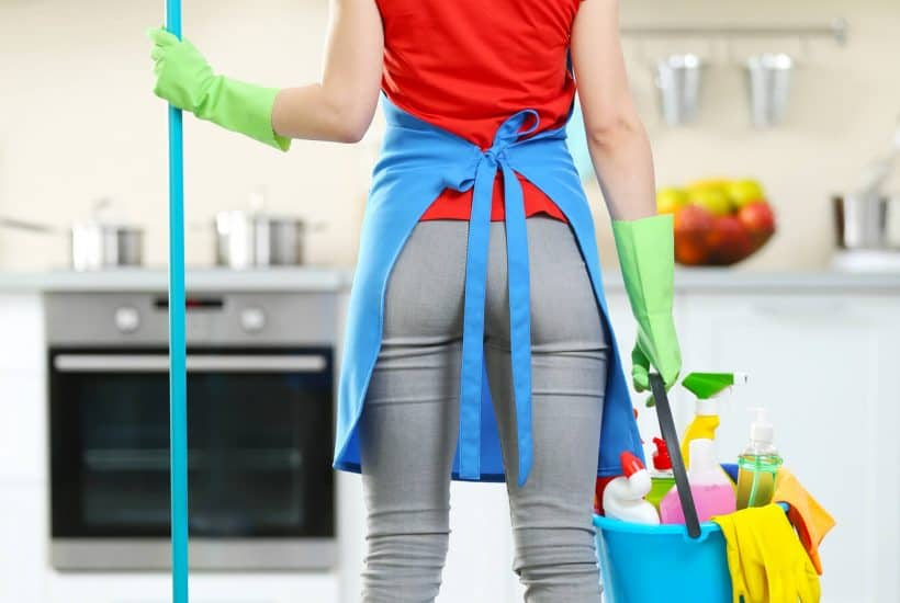 woman standing in kitchen with cleaning supplies