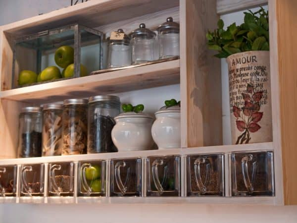 kitchen wall rack with glass jars used to store spices and fruits