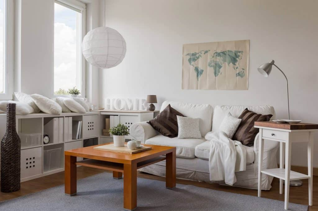 decluttered living room with white couch, coffee table and modular storage