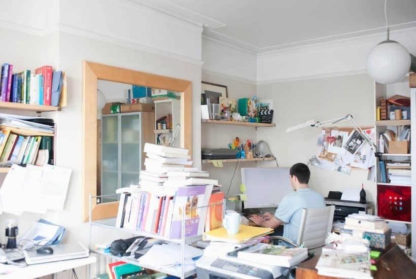home office full of paper clutter stacks