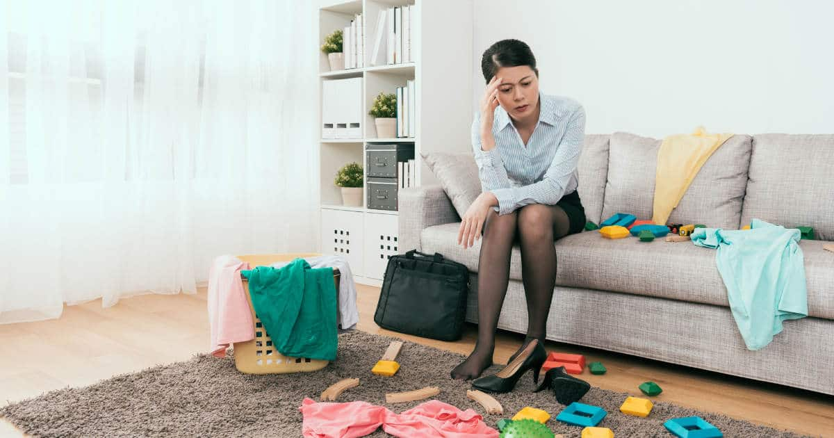 woman sitting in messy living room trying to figure out where to start decluttering