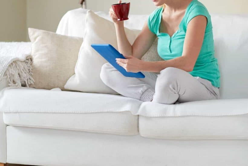 lady sitting on the couch with a cup of coffee while a robot vacuum cleans the floors