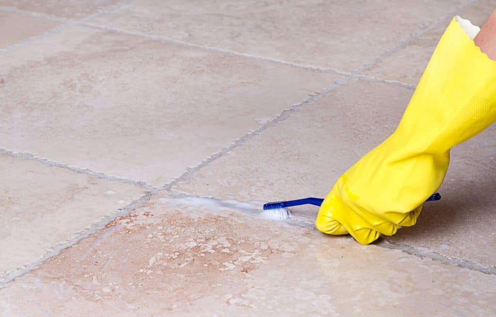 gloved hand cleaning tile floor grout with hydrogen peroxide and a toothbrush