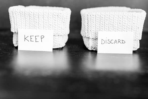sorting baskets labeled 'keep' and 'discard' used during decluttering