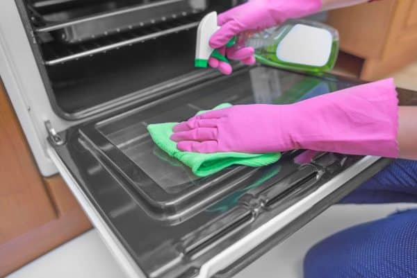 Woman wearing kitchen gloves and cleaning the oven door