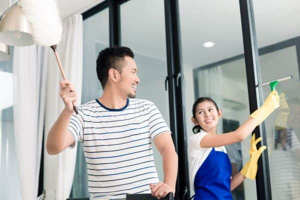 Couple dusting and washing windows as part of their spring cleaning checklist