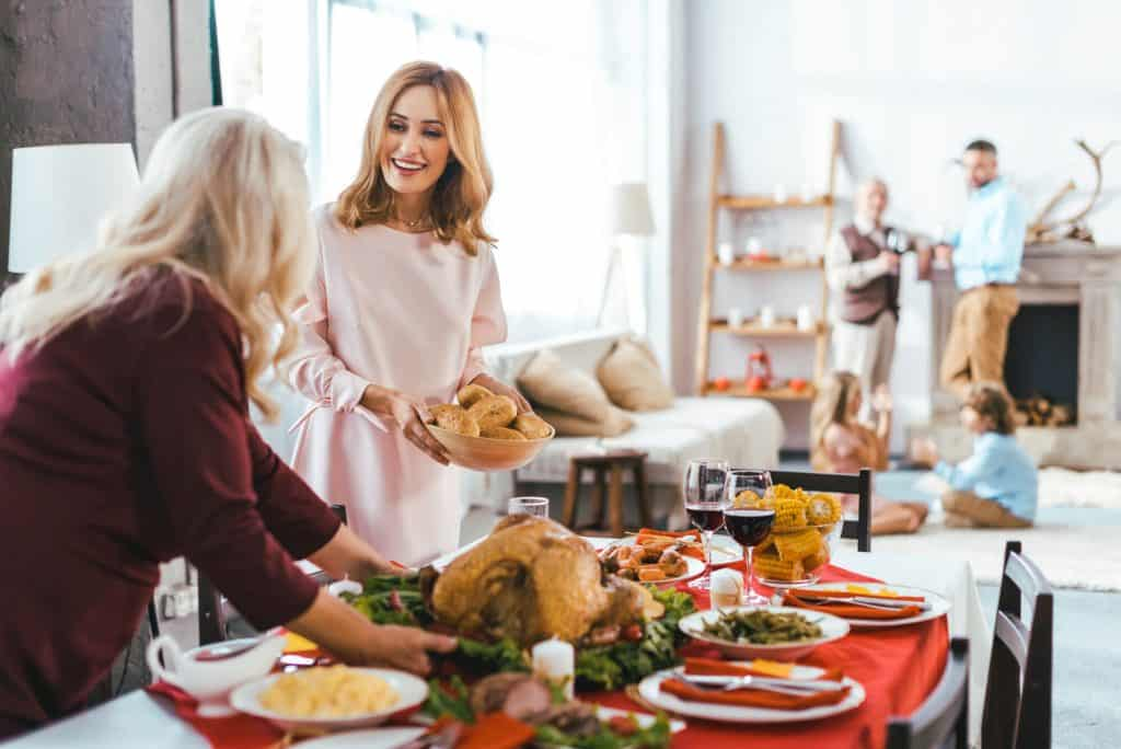 Women serving a stress-free Thanksgiving meal with family socializing in the background