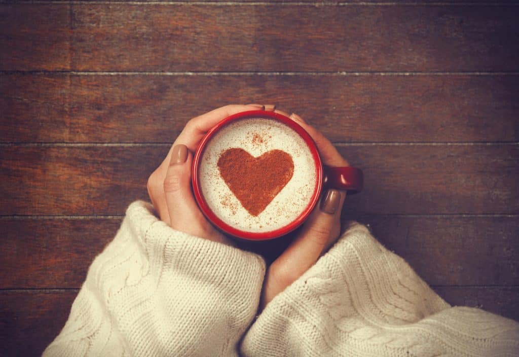 Woman in sweater holding warm cup of cocoa