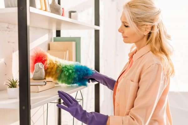 Woman dusting bookshelf while speed cleaning to get ready for company