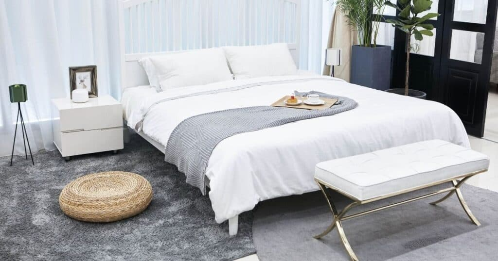 clean, simple bedroom with grey flooring and white bedding