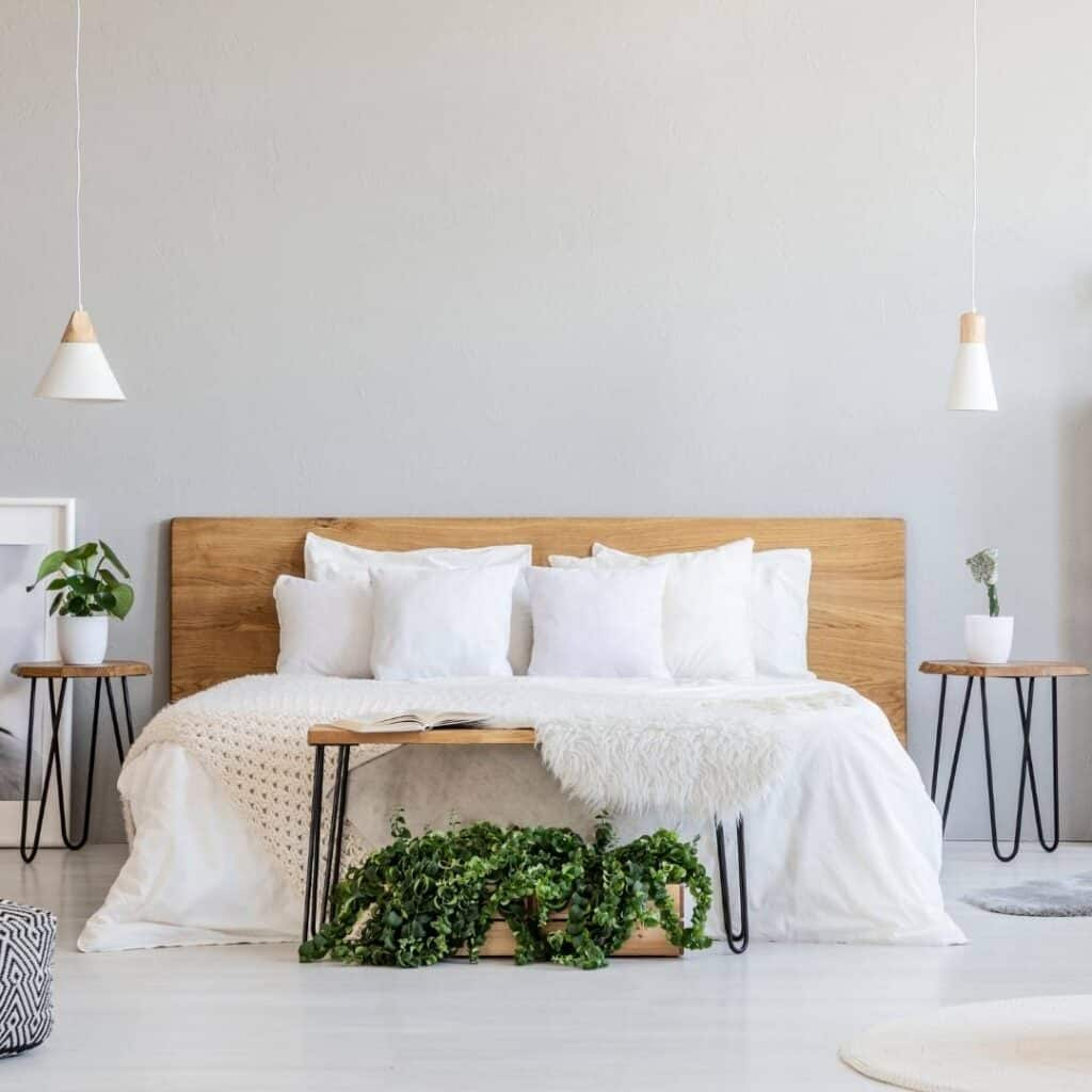 clean and tidy bedroom with white linens, light wood furniture and and light gray walls