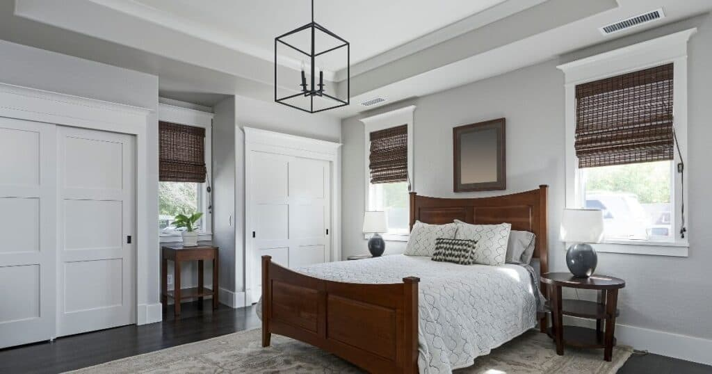 a clean and tidy master bedroom with light gray walls, white trim and dark hardwood floors