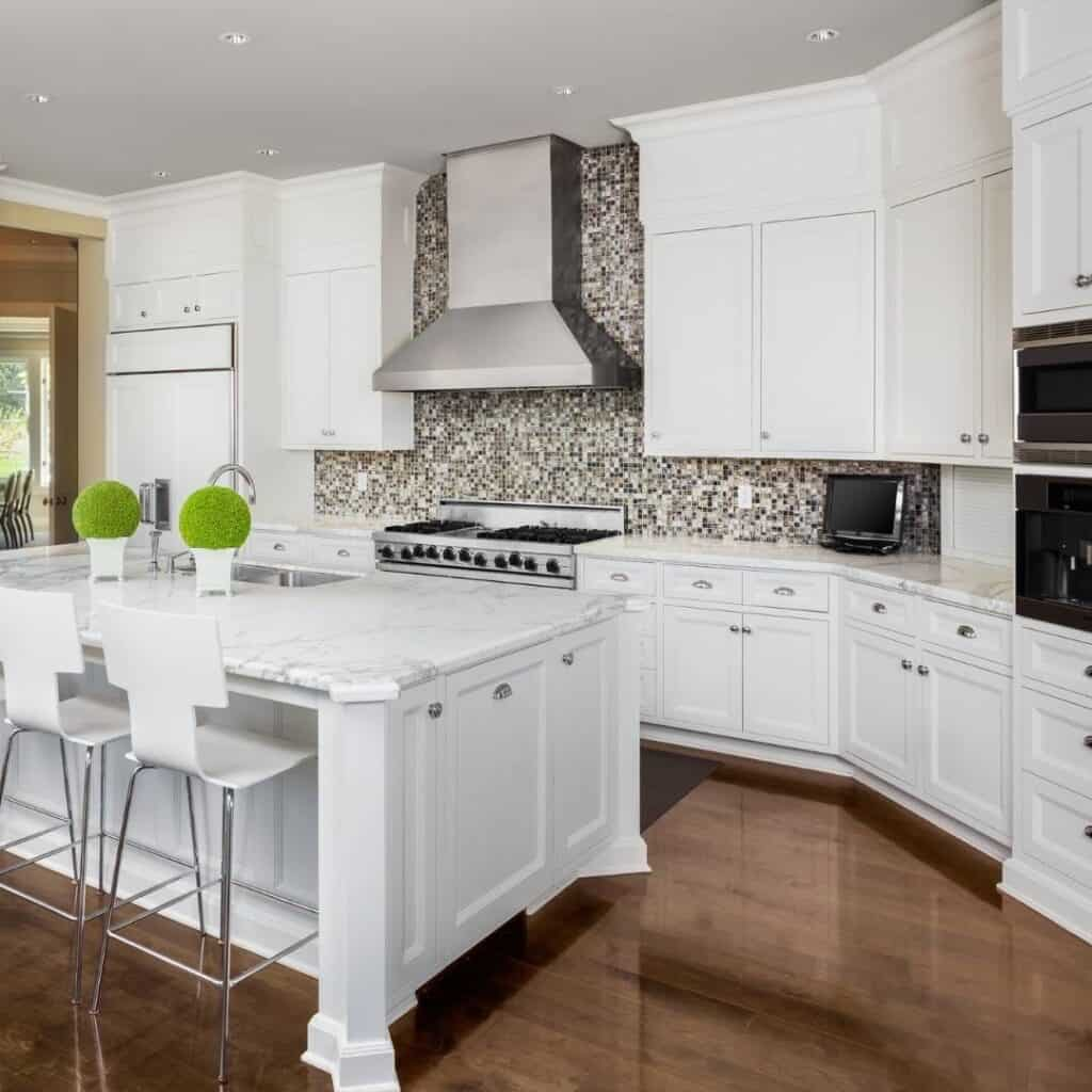 clean kitchen with white cabinets, white marble counters, and wood floors
