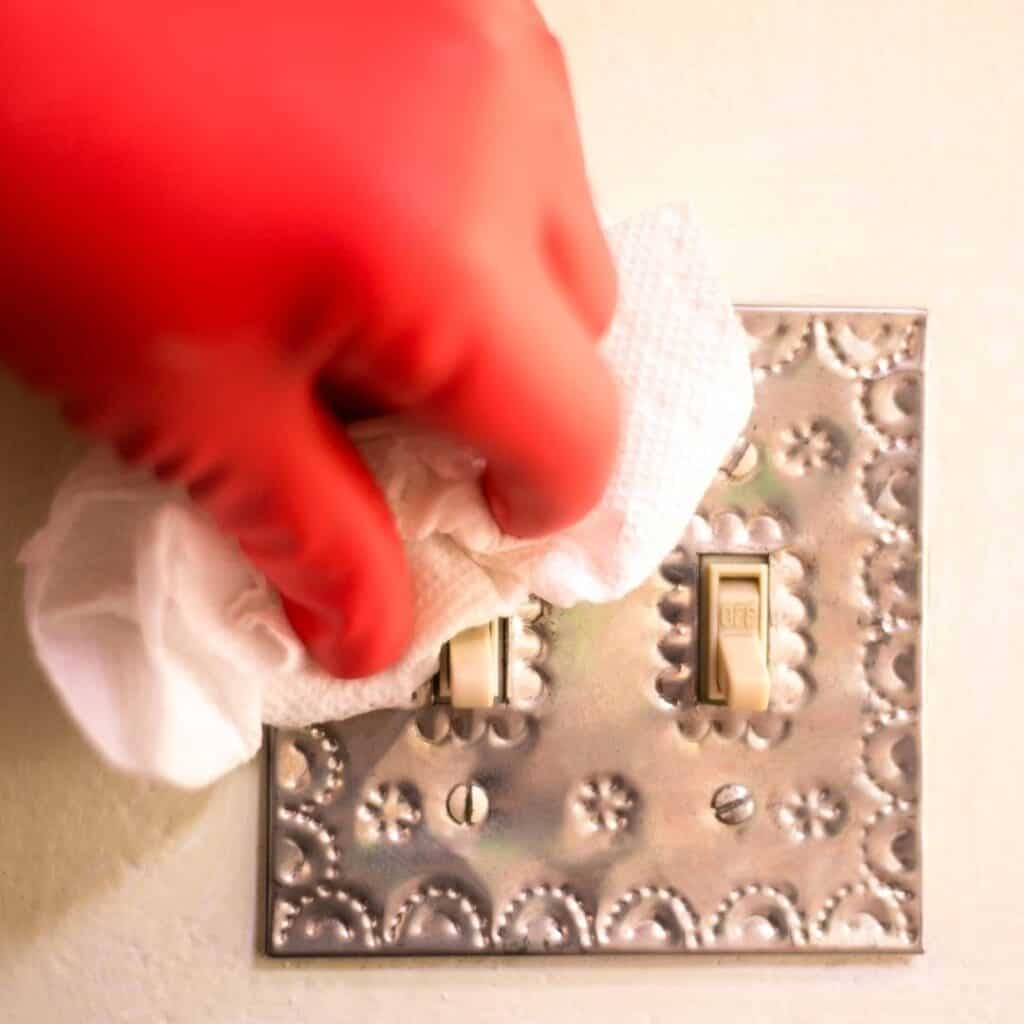 woman cleaning light switches with a disinfecting wipe
