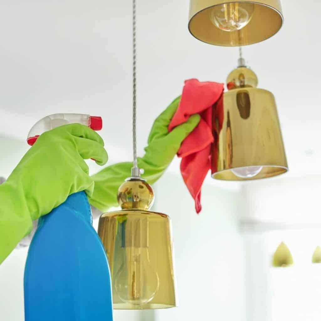 woman deep cleaning kitchen lighting fixtures with a spray bottle and microfiber cloth