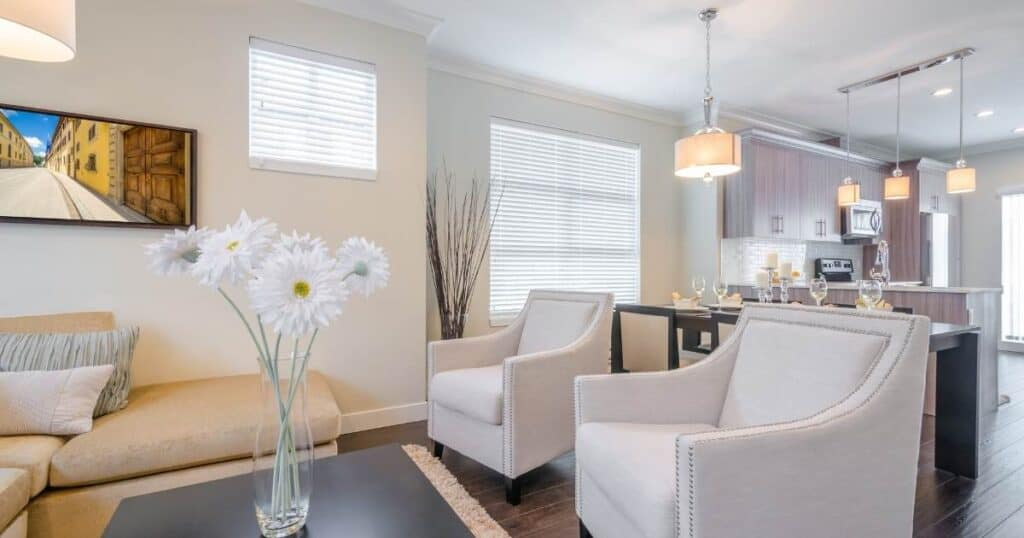 a clutter-free living room with white furniture and a vase of flowers on the coffee table