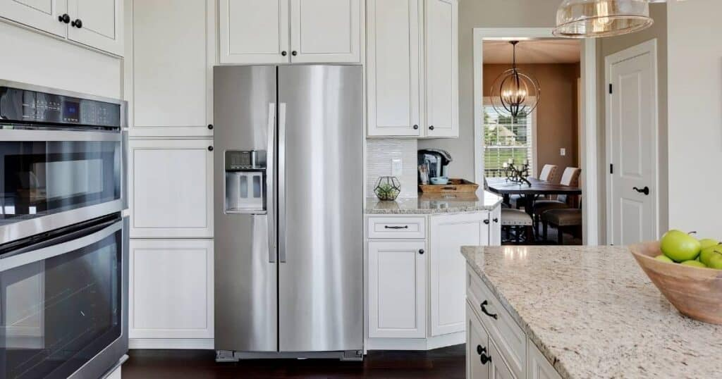 white kitchen with stainless steel french door refrigerator