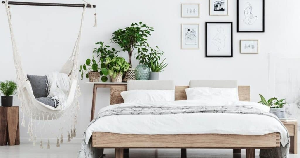 clean and spacious bedroom with white decor, green plants and a platform bed