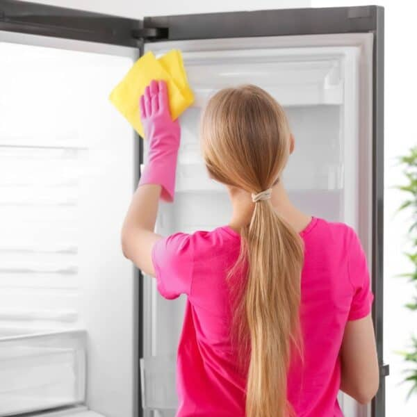 woman deep cleaning the fridge interior surfaces with a microfiber cloth