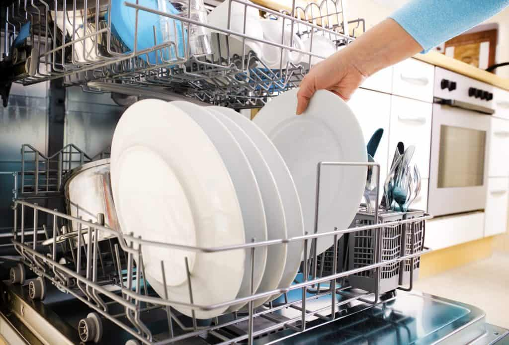 loading dishes in dishwasher to clean kitchen