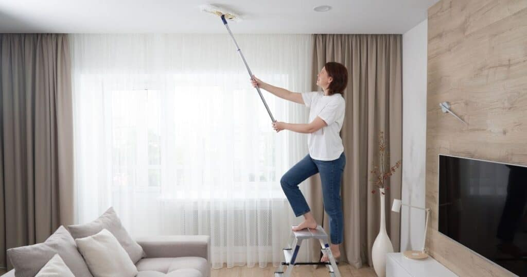 lady dusting ceiling with microfiber mop