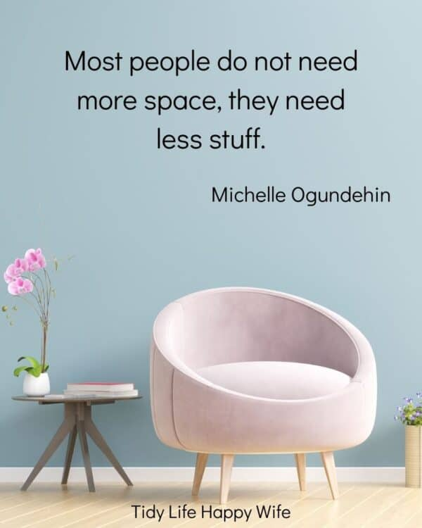 minimal living room with pink chair and wood table, with quote, Most people do not need more space, they need less stuff. by Michelle Ogundehin