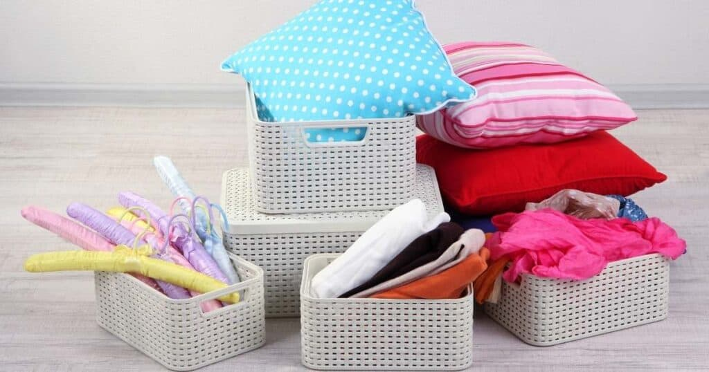 white plastic organizing baskets that are too small and overflowing with stuff