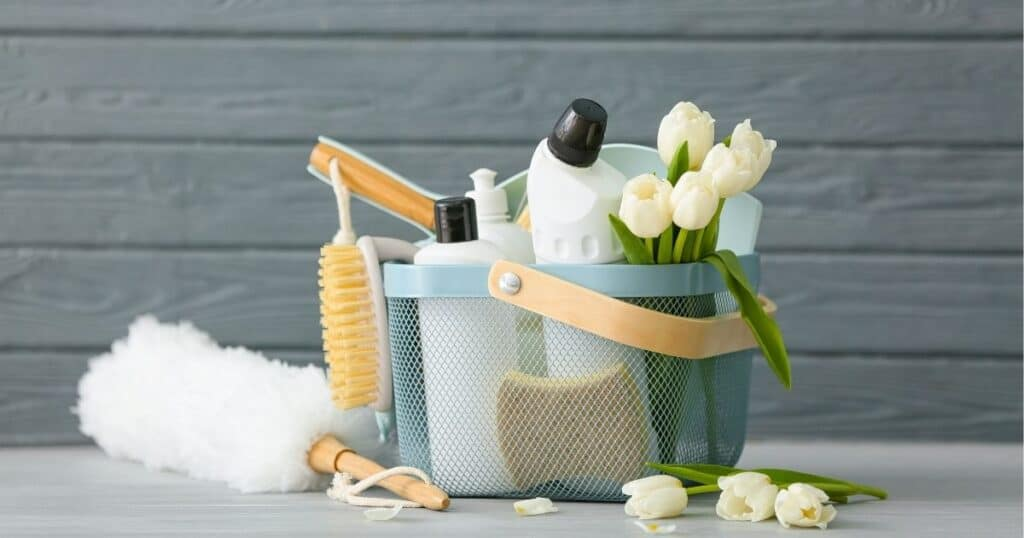 white tulips and spring cleaning supplies in a basket