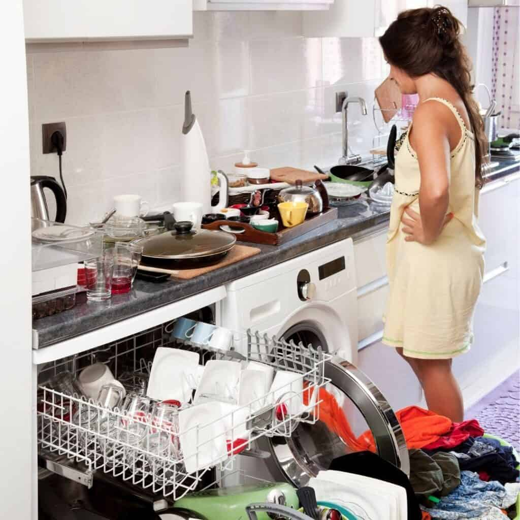 frustrated woman doing dishes and laundry to clean her messy house